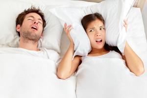 Man snoring in bed due to sleep apnea